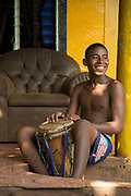 Portrait of a smiling young male local musician sitting and holding drum, Little Corn Island, Nicaragua