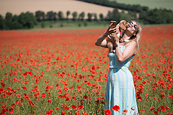 July 7, 2017 - Eynsford, Kent, UK - Eynsford, UK. Londoner Elizabeth Cooper pictured enjoying beautiful Kent poppies on a sunny summer morning in the village of Eynsford with cockapoo puppy Pip. (Credit Image: © Rob Powell/London News Pictures via ZUMA Wire)