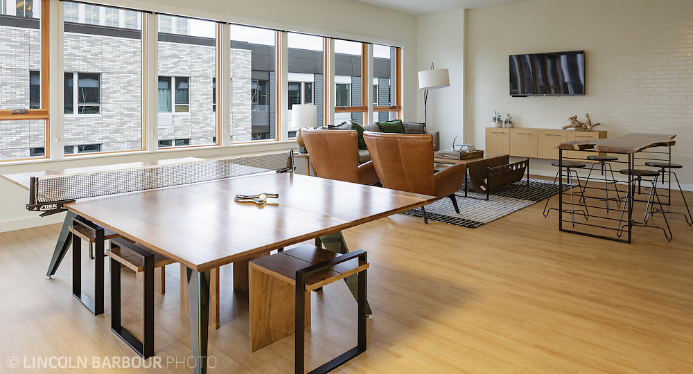 A dining room table doubles as a ping pong table in this nice, upscale apartment living room.