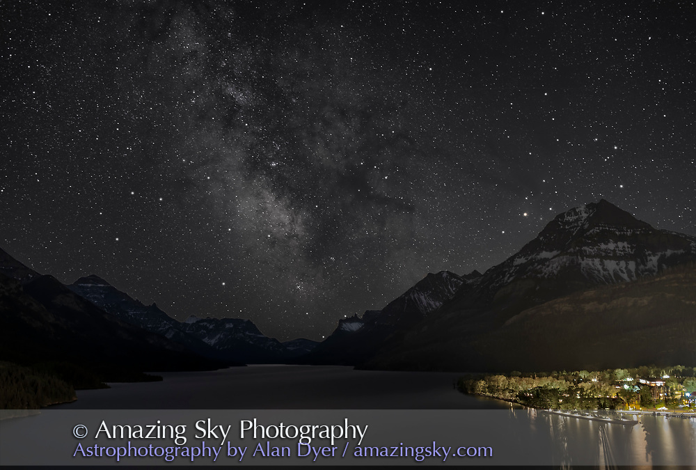 The view of the Milky Way over Upper Waterton Lake in Waterton Lakes National Park, Alberta, processed to resemble the actual naked eye view. <br /> <br /> Scorpius is at right, Sagittarus at centre, with the Galactic Dark Horse and Small Sagittarius Starcloud above. The M6 and M7 star clusters are just above the end of the lake. I shot this on a very clear night, June 1, 2021, from the Prince of Wales Hotel grounds. This image simulates the monochromatic naked-eye view. <br /> <br /> This is a blend of a tracked and untracked exposures: a single 2-minute tracked exposure at ISO 1600 with the MSM Move Shoot Move tracker, with a single 4-minute untracked exposure with the MSM off and at ISO 400, all with the 35mm Canon L lens at f/2.8 and Canon EOS Ra. An additional 30-second exposure at ISO 200 adds the town lighting to prevent that area from being overexposed in the longer exposures. Blended, masked and stacked with Photoshop.
