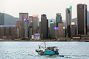 Hong Kong skyling with local fishing boat (junk) leaving for the sea.