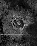 Planet Venus. the Venusian crater Golubkina, a 340 kilometre (20.4 miles) diameter impact crater, contains Magellan data mosaicked with a Soviet Venera 15/16 radar image of the same feature. The Magellan part of the image (right) reveals details of the geology of the crater such as the central peak, the inner terraced walls, and the extremely smooth floor of the crater. The smoothness of the floor may be due to pounding of volcanic lava flows in the crater floor. The rough, blocky morphology of the crater ejecta and the sharp terraced crater wall suggest that this feature is relatively young.