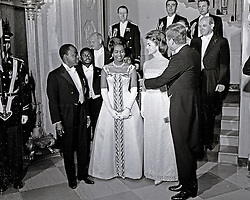 United States President John F. Kennedy and First Lady Jacqueline Kennedy stand in front of the Grand Staircase of the White House in Washington, DC prior to a dinner in honor of President of the Ivory Coast, Félix Houphouët-Boigny, and First Lady of the Ivory Coast, Marie-Thérèse Houphouët-Boigny on May 22, 1962. Front row (L-R): President Houphouët-Boigny; Mrs. Houphouët-Boigny; Mrs. Kennedy; President Kennedy. Others (L-R): Ambassador of the Ivory Coast, Henri Konan Bédié; U.S. Ambassador to the Ivory Coast, R. Borden Reams; Military Aide to President Kennedy, General Chester V. Clifton; Air Force Aide to President Kennedy, Brigadier General Godfrey T. McHugh; Virginia Rusk (mostly hidden); U.S. Secretary of State Dean Rusk ; Naval Aide to President Kennedy, Captain Tazewell Shepard. Photo by Arnie Sachs / CNP /ABACAPRESS.COM