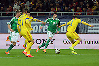 ROMANIA, Bucharest : Romania's Vlad Chiriches (R) and Northern Ireland's Kyle Lafferty (C) vie for the ball during the Euro 2016 Group F qualifying football match Romania vs Northern Ireland in Bucharest, Romania on November 14, 2014.