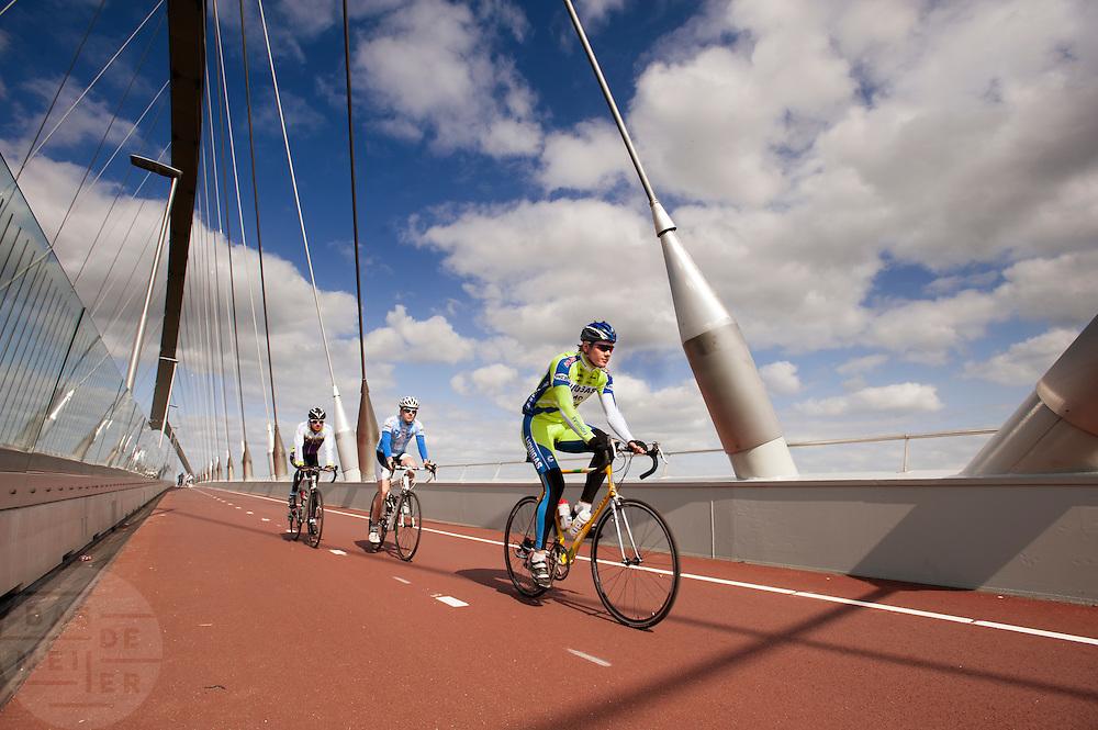 In Nijmegen rijden drie racefietsers op het fietspad aan de Oversteek, de nieuwe verbinding over de Waal aan de noordkant van Nijmegen.<br /> <br /> In Nijmegen cyclists are riding at the bike line at The Crossing, the new connection crossing the Waal at the north side of Nijmegen.