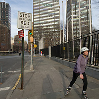 A woman roller skates beside First Avenue near the United Nations Building in New York City.