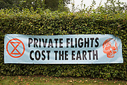 A banner displayed by Extinction Rebellion climate activists outside an entrance to Farnborough Airport is pictured on 2nd October 2021 in Farnborough, United Kingdom. Activists blocked three entrances to the private airport to highlight elevated carbon dioxide levels produced by super-rich passengers using private jets and greenwashing by the airport in announcing a switch to sustainable aviation fuel SAF.