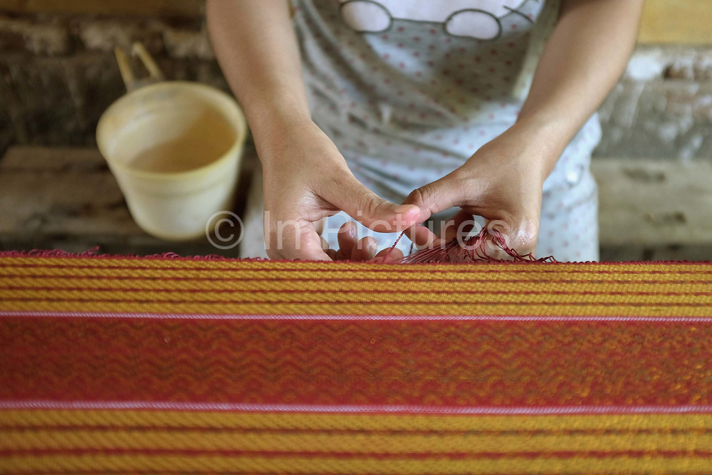 A Hindu Cham woman wearing a Hello Kitty t-shirt creates a fringe on a piece of narrow handwoven cotton and silk fabric outside her home in My Nghiep village, Ninh Thuan province, Central Vietnam. The fabric is used as a decoration during Cham religous ceremonies. The Cham people are remnants of the Kingdom of Champa (7th to 18th centuries) and are recognised by the government as one of Vietnam's 54 ethnic groups.