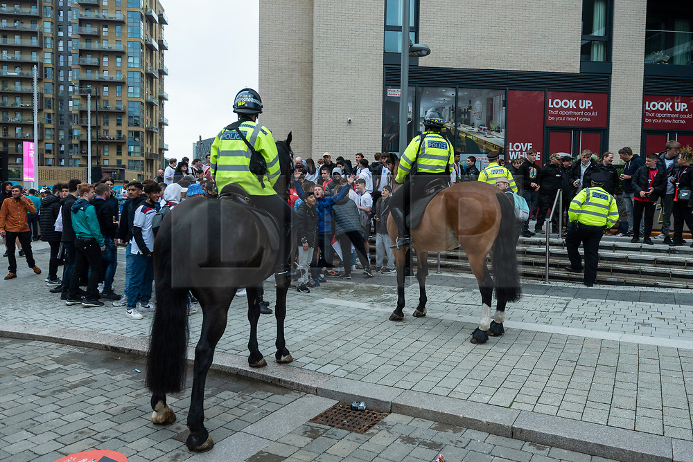 © Licensed to London News Pictures. 18/06/2021. LONDON, UK.  Police monitor England football fans arriving for the Euro 2020 Group D match between England and Scotland match at Wembley Stadium. The tournament was postponed from 2020 due to the COVID-19 pandemic in Europe and rescheduled for 11 June to 11 July 2021 with matches to be played in 11 cities. Wembley Stadium will host certain group matches, as well as the semi-finals and final itself.  Photo credit: Stephen Chung/LNP
