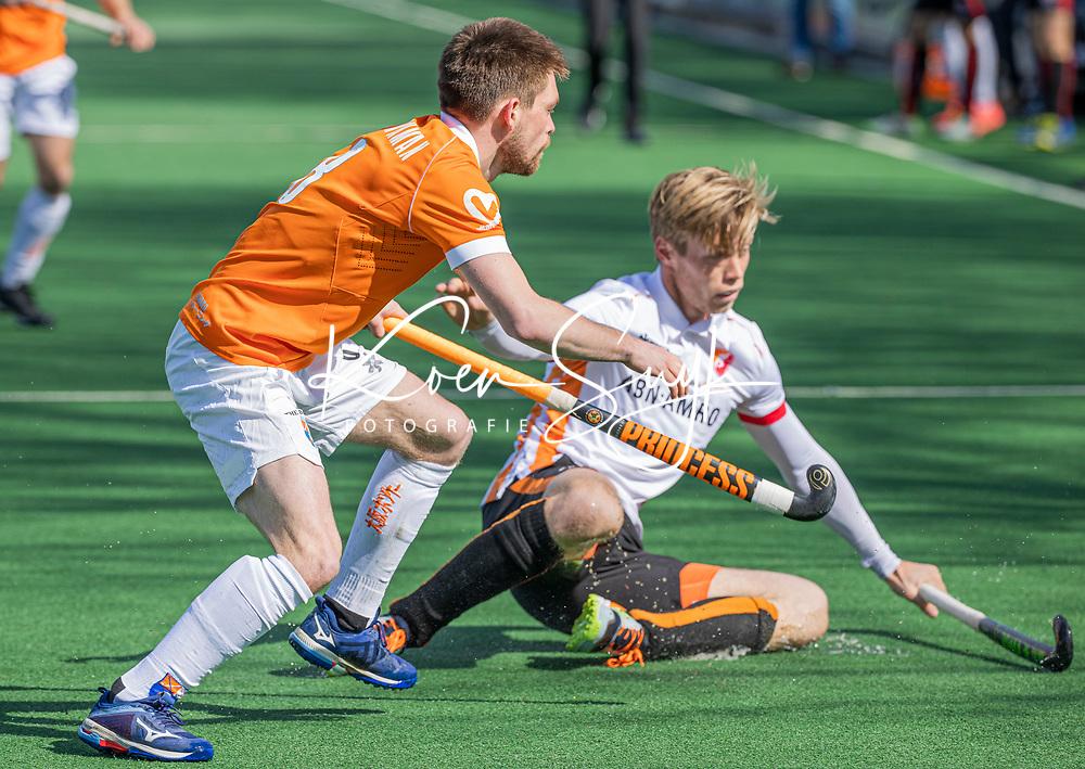 BLOEMENDAAL - Thierry Brinkman (Bldaal) met Max de Bie (Oranje Rood)    tijdens de hoofdklasse hockeywedstrijd dames , Bloemendaal-Oranje Rood  (3-1).  COPYRIGHT  KOEN SUYK