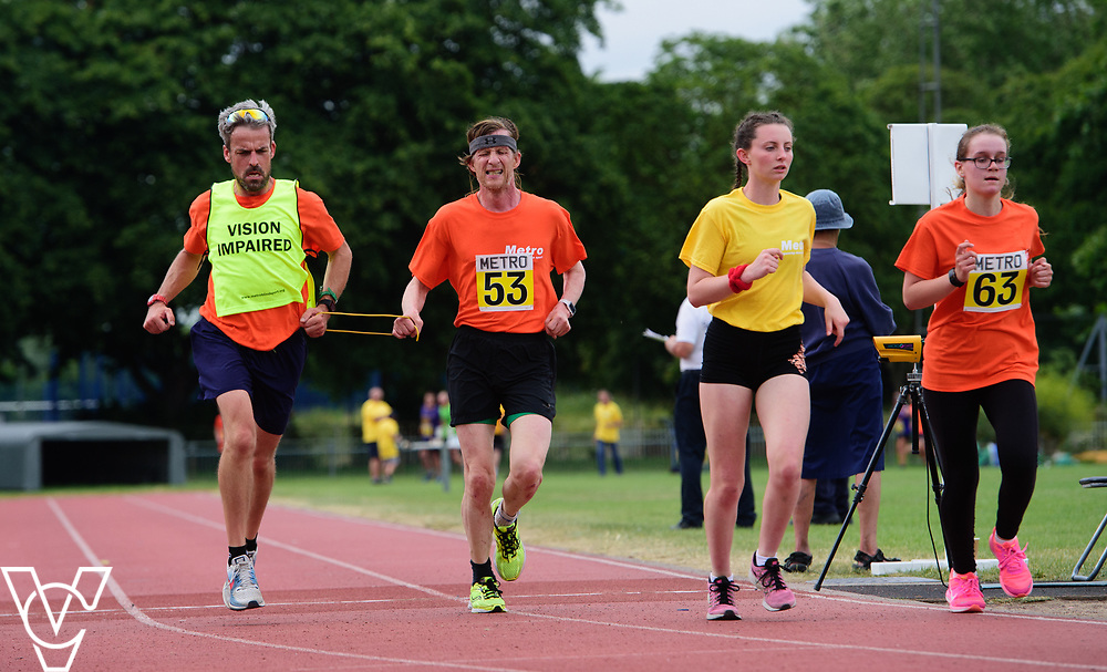 Event: 5000 meter relay<br /> Competitors, from left: Neil Foster and Rebecca Blakey<br /> <br /> Metro Blind Sport's 42nd Athletics Open, held at Mile End Stadium, Tower Hamlets, London.<br /> <br /> Picture: Chris Vaughan Photography for Metro Blind Sports<br /> Date: June 16, 2018