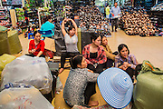 01 APRIL 2012 - HANOI, VIETNAM: Laborers wait for work at Dong Xuan Market, one of the largest markets in Hanoi, the capital of Vietnam. The market The market was originally built by French colonial authorities in 1889. It was renovated in 1990 but burnt to the ground in 1994. The present building was built in 1996.    PHOTO BY JACK KURTZ