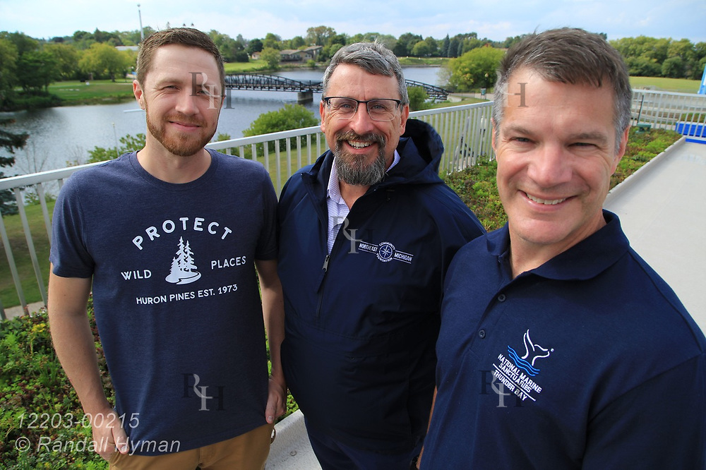 Huron Pines communications associate Chris Engle, Community Foundation for Northeast Michigan executive director Pat Heraghty, and Thunder Bay National Marine Sanctuary superintendent Jeff Gray pose atop green roof of NOAA's Great Lakes Maritime Heritage Center in Alpena, Michigan.