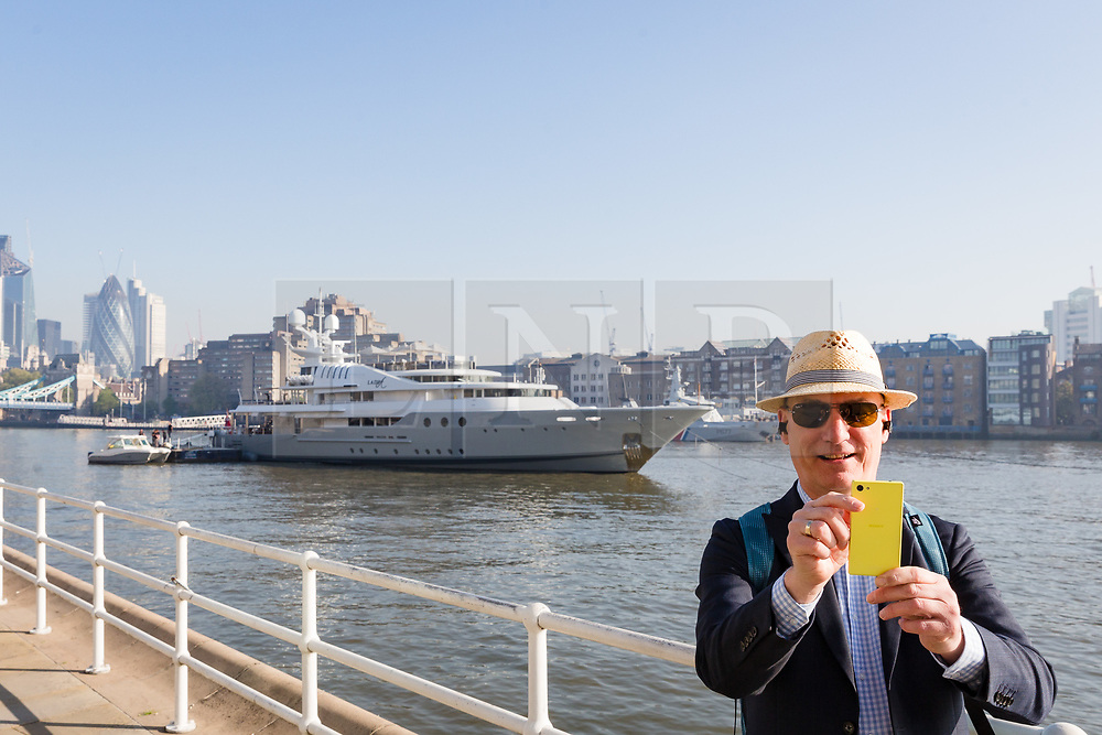 © Licensed to London News Pictures. 08/05/2018. London, UK. A man takes a photograph of Lady A superyacht moored at Butlers Wharf during sunny weather this morning near Tower Bridge on the River Thames in London. The 181 feet long, Lady A superyacht is owned by Alan Sugar, named after his wife, Anne and is currently up for sale, reportedly at £13m.  Photo credit: Vickie Flores/LNP