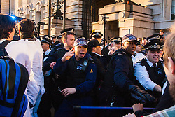 London, March 7th 2015. Following the Climate march through London, masked anarchists and environmental activists clash with police following a breakaway protest at Shell House. PICTURED: Police officers attempt to clear a path for their van containing an arrested anti-fracking protester, blocked in by activists.