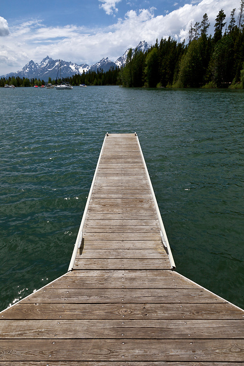 Dock on the Waters edge at Colter Bay on Jackson Lake with the Teton Mountain Range in Teton National Forest on beautiful calm spring morning from Colter Bay. Licensing and Open Editions