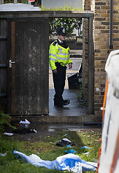© Licensed to London News Pictures. 24/05/2021. London, UK. A police officer stands guard in the garden of a property at Consort Road, Peckham in south London near where Black Lives Matter activist Sasha Johnson was shot. Ms Johnson remains in a critical condition in hospital after the shooting which happened at 3am on Sunday morning. Photo credit: Peter Macdiarmid/LNP