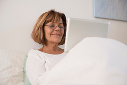 Senior woman sitting on bed and using a digital tablet, Munich, Bavaria, Germany