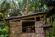 Children sheltering from the rain in the forest near Piscina Beach in São Tomé.