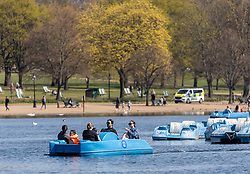 Licensed to London News Pictures. 19/04/2021. London, UK. Members of the public soak up the sunshine on the Serpentine in Hyde Park, London a week after the easing of Covid-19 restrictions as a mini heatwave hit the UK this week with temperatures reaching up to 18c in London and the South East. Photo credit: Alex Lentati/LNP