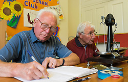 © Licensed to London News Pictures.04/08/15<br /> Egton, UK. <br /> <br /> <br /> Weigh men COLIN GRAY (L) and HARRY HEBDON check and note down the weight of one of the gooseberries during judging at the annual Egton Gooseberry Show. <br /> There are only two Gooseberry societies left in the country. One in Cheshire and one at Egton in North Yorkshire. The annual show in Egton uses traditional Avoridupois scales to measure the weight of the berries and members of the society are fanatical about trying to grow the best berries each year. <br /> <br /> Photo credit : Ian Forsyth/LNP