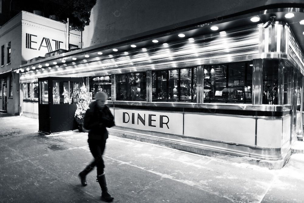 Woman walking in fron of the former Empire diner in the Meatpacking district at night. This neighbourhood of Manhattan that runs from the West 14steet to Gansevoort street and from the Hudson river to the Hudson street was at the beginnings of the XX century an area where more than 250 slaughterhouses and meat packing business operated. Nowadays it is a trendy district with a lot of expensive clothing boutiques fusion restaurants and an expanding nightlife that has converted this neighbourhood in a fashionable part of the city.