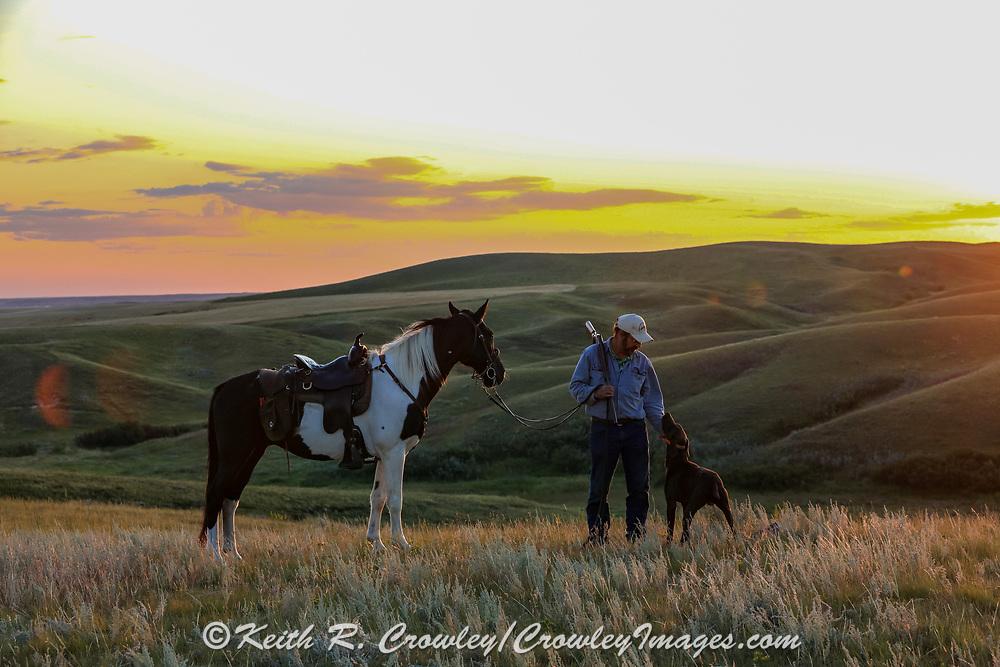 John Zeman,  his German shorthair Louie, and his horse Buckwheat return to camp at sunset during a Montana prairie grouse hunt.