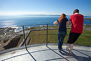 A young couple look out to sea from the Hook Lighthouse, Fethard on Sea, Wexford, Irelan, one of the oldest lighthouses in the world, which has been in use since the 12th or 13th century. Although a fire beacon was operated here to warn shipping as early as the 5th century, it was with the arrival of the Normans in that the tower was built. The existing lighthouse incorporates the original Norman fortress structure.