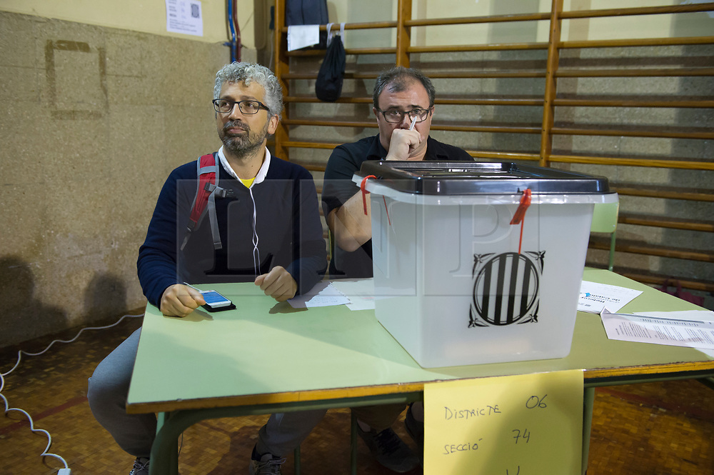 """© Licensed to London News Pictures. 01/10/2017. Barcelona, Spain.  <br /> <br /> Members of the organization during the voting at Sedeta de Gracia´s Centre Civic poll station.<br /> <br /> Students, their parents, associations and neighbours have organized to carry out """"playful activities"""" during the weekend and keep open the Sedeta de Gracia´s Centre Civic.<br />  <br /> Since early in the morning dozens of people wait at the college´s door for the voting time under the rain.<br /> <br /> Mossos d´Escuadra said they won´t do nothing if that can destabilize social order.<br /> <br /> Catalonia is awaiting for today, October 1st, when the Spanish Region wants to vote in a self-determination referendum to get a independence.<br /> <br /> The Referendum´s Law was passed on last September 6th at the Catalonian Parliament thanks to the votes of """"Junts pel Sí"""" and """"CUP"""". Then it was suspended by the Spanish Constitutional Court, on next day.<br /> Carles Puigdemont, the President of the Government ofCatalonia, said he would ignore that and he and his Government will continue with the Referendum.<br /> <br /> The Spanish Government has sent to Catalonia thousands of """"Guardia Civil"""" and """"Policía Nacional"""" officers (two of the Spanish forces and state security forces), to enforce the ruling of the Constitutional Court and avoid the voting process on next Sunday. They will work with the Mossos d´Escuadra (the Autonomic police in Catalonia).<br /> <br /> To avoid the vote, the Spanish Government has prevented the opening of polling stations, some of which are schools.  <br /> <br /> Photo credit: Gustavo Valiente/LNP"""