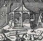 Furnace for refining copper with all the tools necessary to carry out the process.  From 'De re metallica', by Agricola, pseudonym of Georg Bauer (Basle, 1556).  Woodcut.