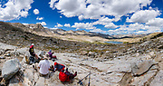 Hikers eat lunch on Piute Pass, overlooking Desolation Lake in Humphreys Basin in John Muir Wilderness, Inyo National Forest, California, USA (9.7 miles round trip, 2200 ft gain). Multiple overlapping photos were stitched to make this panorama.