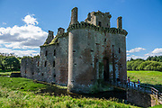 """The formidable red sandstone walls of Caerlaverock Castle have a triangular shape, unique in Britain. First built in 1295 to to control trade, its wide moat, twin-towered gatehouse and lofty battlements give Caerlaverock a fairtale appearance, the epitome of a medieval stronghold. In the castle courtyard, walk through Nithsdale Lodging, a remarkable residence built in 1635, """"the most ambitious early classical domestic architecture in Scotland."""" Caerlaverock is near Dumfries, on the edge of Caerlaverock National Nature Reserve, in southwest Scotland, United Kingdom, Europe. This stronghold defended the Maxwell family from the 1200s-1640, then was abandoned. It was besieged by the English during the Wars of Scottish Independence, and underwent several partial demolitions and reconstructions from the 1300s-1400s."""