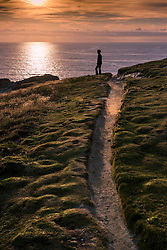 A woman stands on Porth Island looking out to sea at a spectacular sunset.