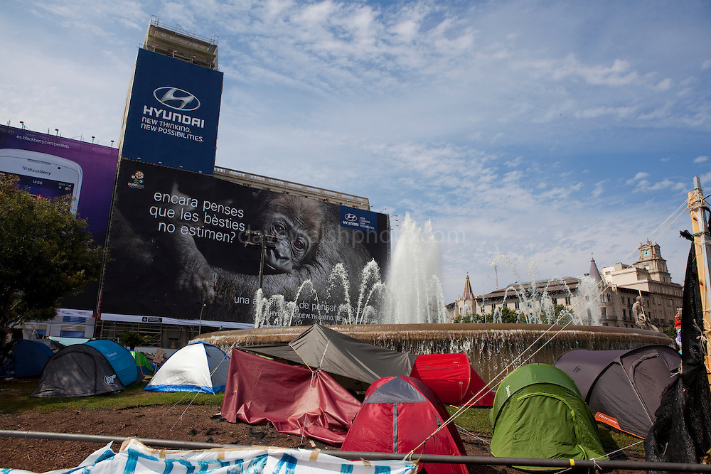 "Protest camp at Placa de Catalunya, Barcelona, Spain. Behind is a Hyundai advertisement, which reads ""Still believe that animals do not love? Another way of thinking is possible"".. Behind is a Hyundai advertisement, which reads ""Still believe that animals do not love? Another way of thinking is possible"". The square has been relatively quiet since police attacked and beat protestors on May 27 2011."