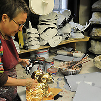 An artisan  works with gold leaf on a mask. Artisans, masks and costumes makers are getting ready ahead of Venice Carnival 2013