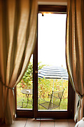A hotel room with a view looking out onto vineyards on an Italian wine estate, near La Morra (Piedmont), Italy.