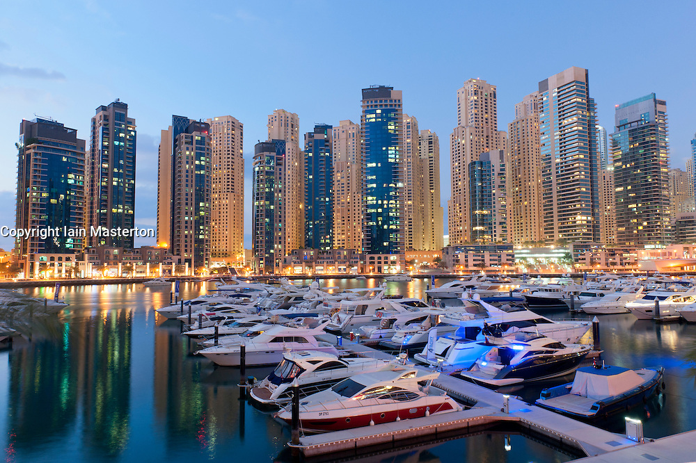 Boats in harbour in the evening at Yacht Club Marina with apartment towers to rear in New Dubai in United Arab Emirates