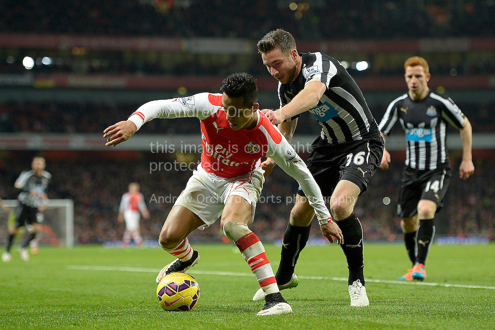 Alexis Sanchez of Arsenal holding the ball from Paul Dummett of Newcastle United. Barclays Premier league match, Arsenal v Newcastle Utd at the Emirates Stadium in London on Saturday 13th December 2014.<br /> pic by John Patrick Fletcher, Andrew Orchard sports photography.