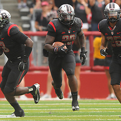 Oct 6, 2012: Rutgers Scarlet Knights linebacker Khaseem Greene (20) runs back an interception with blockers during second half NCAA college football action between the Rutgers Scarlet Knights and UConn Huskies at High Point Solutions Stadium in Piscataway, N.J.