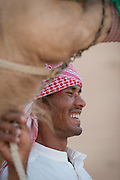 Man, with camel in the desert near Dubai, United Arab Emirates