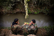 Afghan army soldiers share grapes beside a small canal after arriving to reinforce US troops  at COP Nolen, in the volatile Arghandab Valley, Kandahar, Afghanistan, Thursday, July 22, 2010. (AP Photo/Rodrigo Abd)
