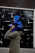 Father and child with a background of a geometric-designed wall in central London