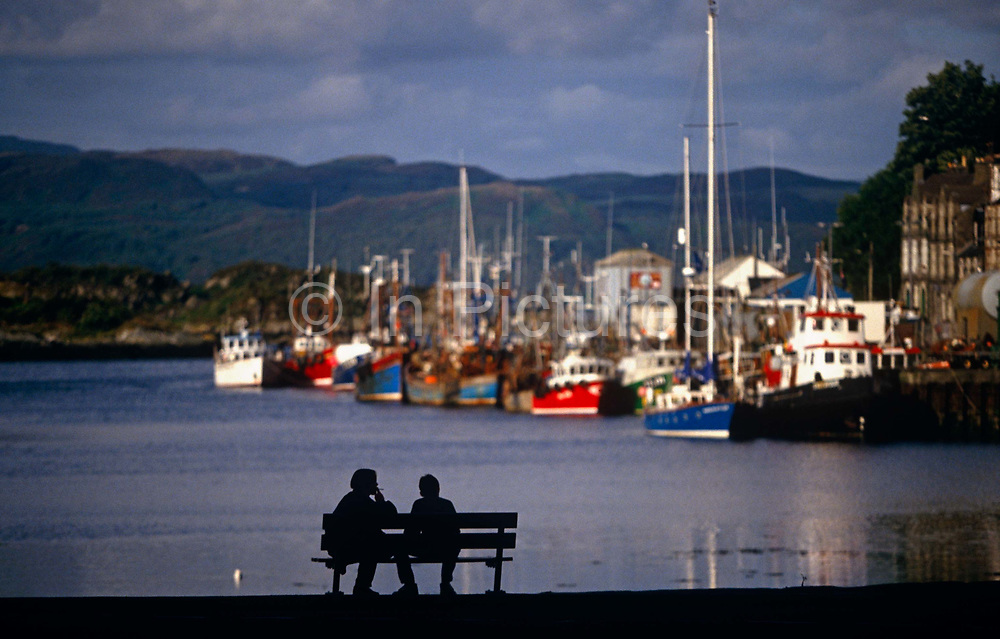 The fishing fleet of Tarbert on Scotland's Mull of Kintyre lies moored at the dock of this pretty coastal village in the Western Isles. Their colourful hulls shine in late afternoon sunshine as they are tied up awaiting another outing at sea to provide for this small fishing community a living and a livelihood for its families. But in the foreground sit a young couple whose prospects are not so positive: they rest on a bench in silhouette, one smoking a cigarette while turned to the friend who stares out to distant rolling hills. It is a scene of hopelessness that reflects modern life for the youth in remote communities where jobs are scarce and their futures far from secure. In an otherwise idyllic Scottish landscape, we guess at the disintegration of society up here - the scourge of economic downturn and future social problems.