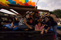 Stock photo of kids with painted faces riding in the back of a truck.