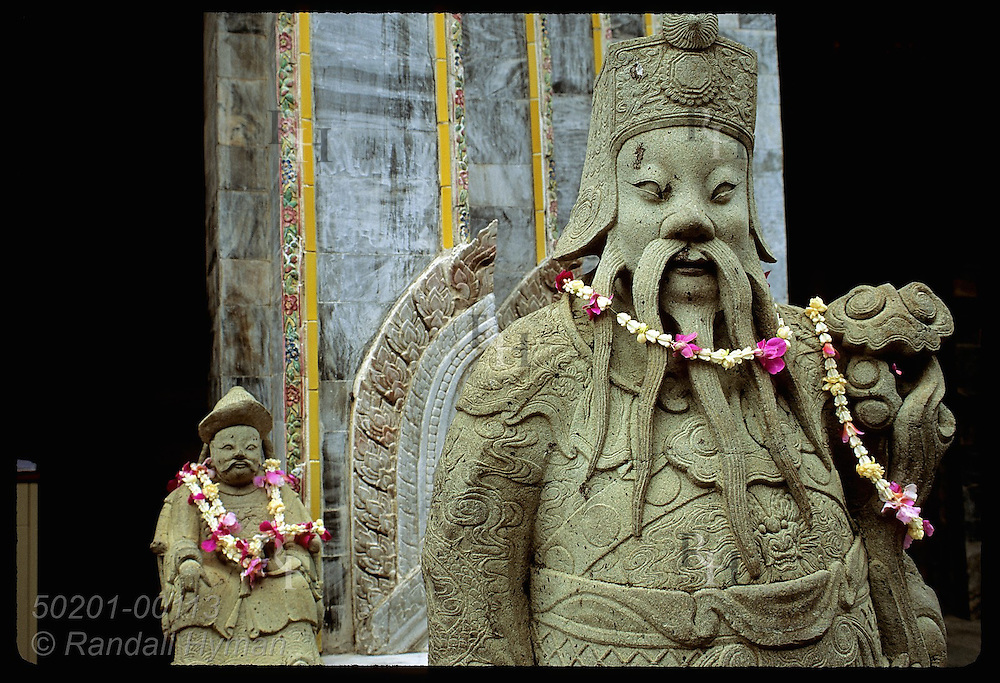 Necklaces of garlands and orchids adorn stone Buddhist statues in Grand Palace compound;Bangkok Thailand