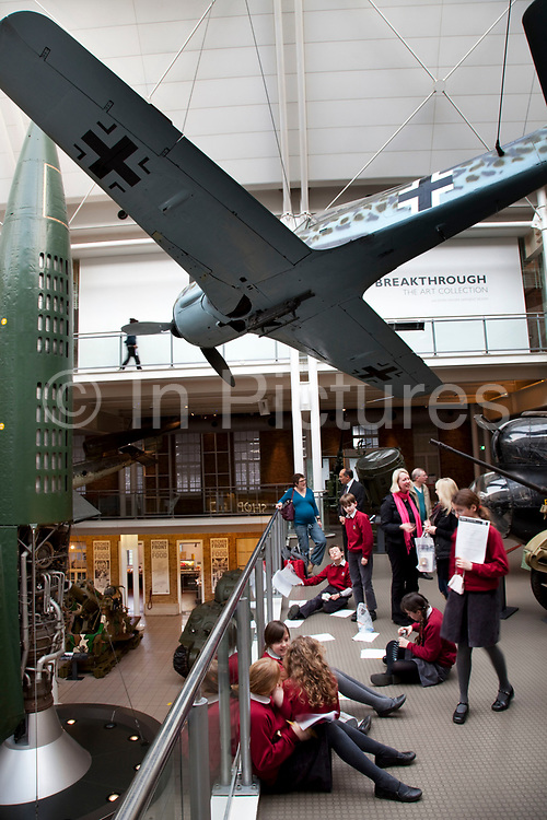 German Focke-Wulf Fw 190 fighter. View inside the main atrium at the Imperial War Museum, London. Aircraft from the First and second World Wars are suspended from the ceiling as are various armaments.