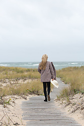 blond girl walking on a wooden beach walkway during the winter towards the ocean