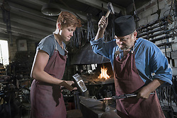 Blacksmith and apprentice hammering red hot iron bar at workshop, Bavaria, Germany