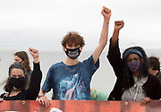 Protesters gtaher on Gyllyngvase beach, Cornwall, as the Youth Strike for Climate happens for the first time since the Pandemic. 11th June 2021. Anna Hatfield/Pathos