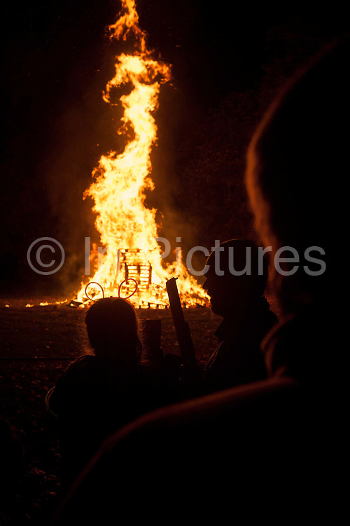 Dark figures stand in silence to watch the crackling flames of a bonfire during the annual bonfire night on 5th November 2016, in Kington, Herefordshire, England. Bonfire night is an annual English tradition that takes across Engliand, especially in rural towns and villages such as Kington, a farming community on the English/Welsh border. The tradition is to light a bonfire with a guy on top historically, an effigy of Guy Fawkes, the Catholic plotter against King James 1, in 1605 although nowadays, the effigy can be of any hate character. This year, it was of Donald Trump - a few days before his shock election victory. Soon afterwards, the fireworks display was under way.